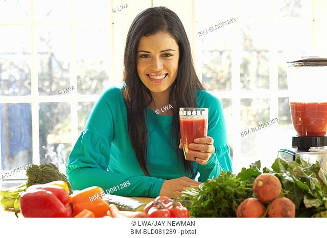 Hispanic woman drinking vegetable juice