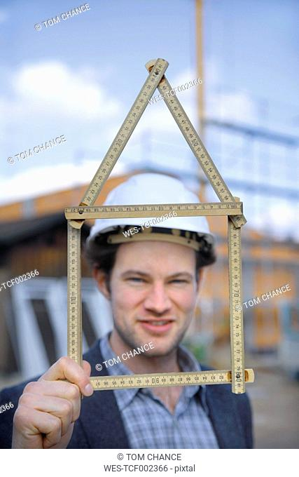 Germany, Bavaria, Young man with hard hat showing pocket rule at construction site
