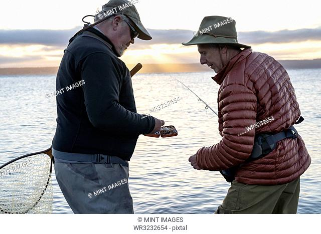 A male fly fisherman watches his guide work putting on a new fly to try for salmon or trout at a salt water beach