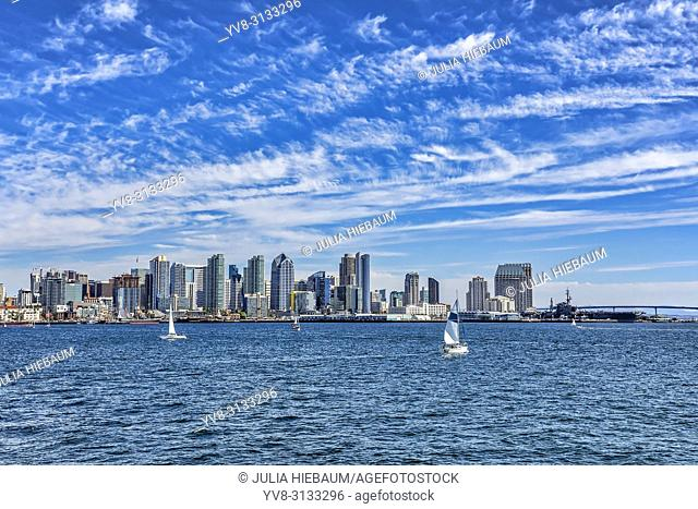 Sailboats gliding by Harbor Bay in San Diego, California