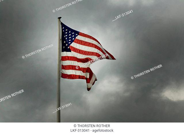 American flag agains cloudy sky