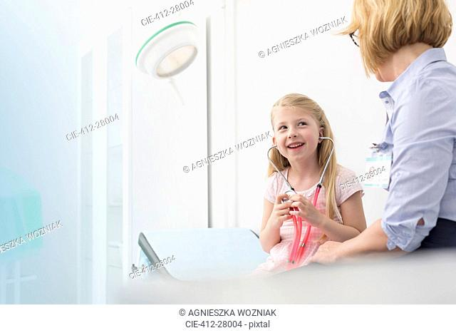 Pediatrician watching girl patient playing with stethoscope in examination room