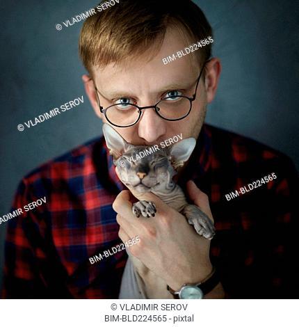 Caucasian man kissing kitten