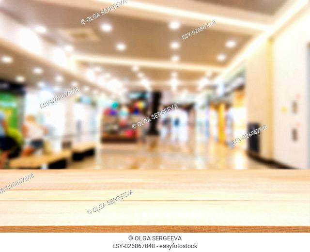 Wooden board empty table in front of blurred background. Perspective light wood table over blur in shopping mall hall. Mock up for display or montage your...