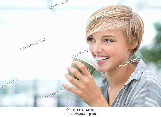 Young woman drinking takeaway coffee in city