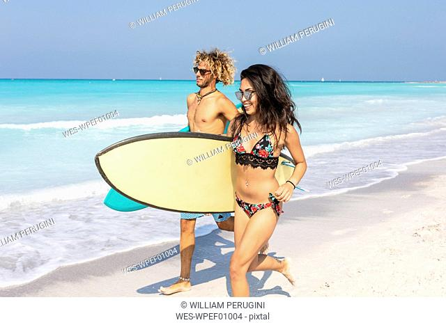 Couple running on the beach, carrying surfboards