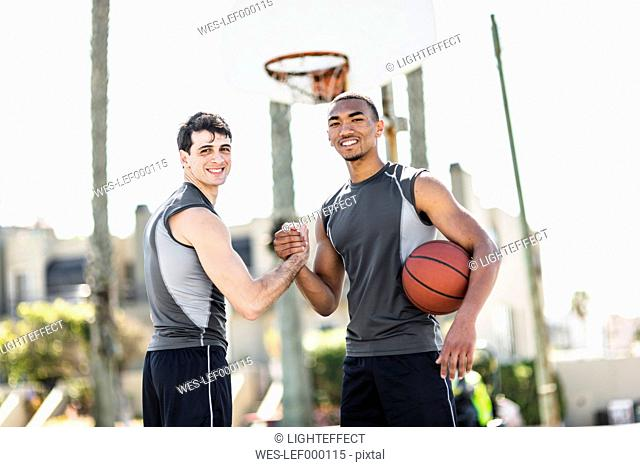 Two young men shaking hands on outdoor basketball court