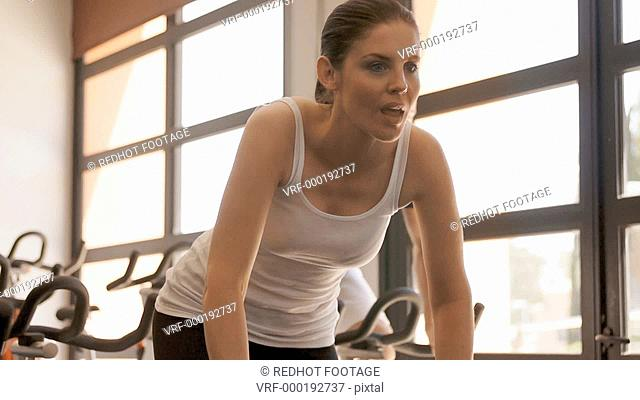 Dolly shot of young couple on exercise bikes at gym