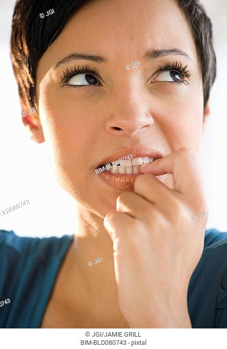 Mixed race woman with short hair biting fingernail