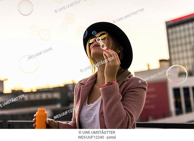 Young woman in the city blowing soap bubbles in the evening