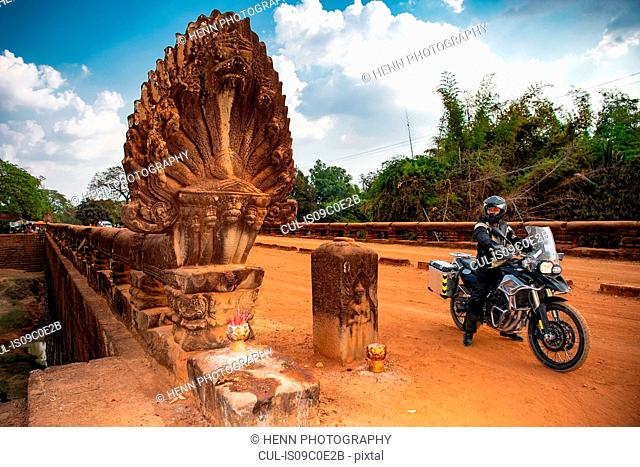 Men riding ADV motorcycles taking a break on the Kampong Kdei or dragon bridge in Cambodia