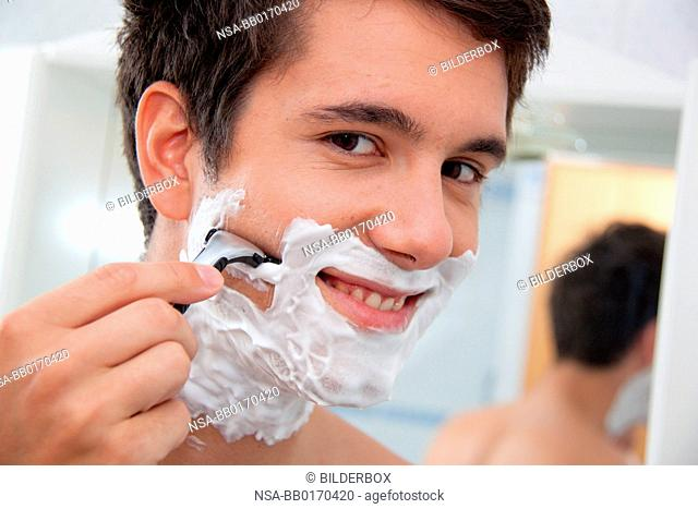 Young man shaving with razor and shaving cream in the bathroom