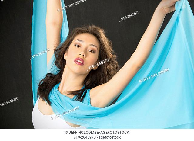 Beautiful young woman dancer in light blue cape and white leotard, half length with arms up against black background, horizontal image