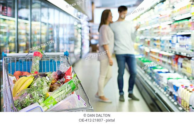 Defocussed view of couple shopping in grocery store