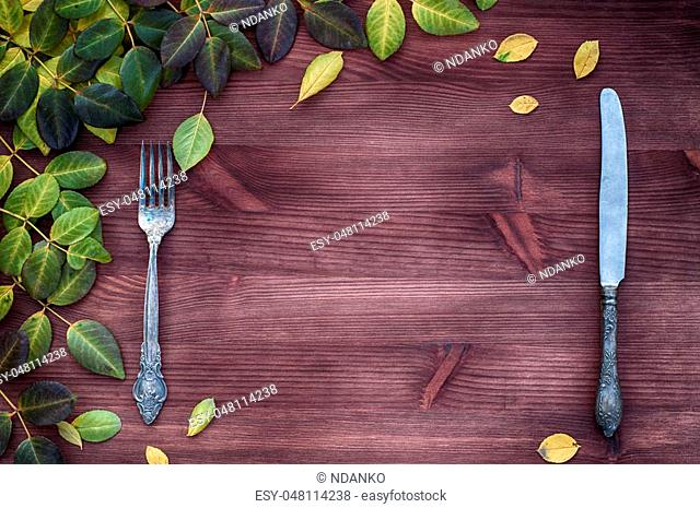 Knife and fork on a brown wooden surface, empty space in the middle, branches of leaves in the upper right corner