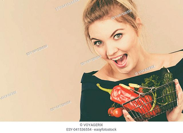 Buying good food, vegetarian products. Positive woman holding shopping basket with green red vegetables inside, recommending healthy high fibre diet