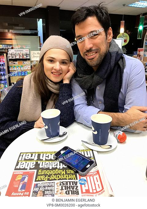 couple taking a break at table at gas station's café with newspaper Bild and smartphone laying on table and paper cups of coffee in Munich, Germany