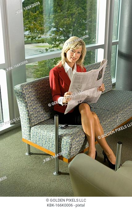 Portrait of a smiling businesswoman sitting in a lobby reading a newspaper