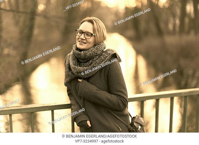 woman outdoors at bridge over river, at public park Englischer Garten in Munich, Germany