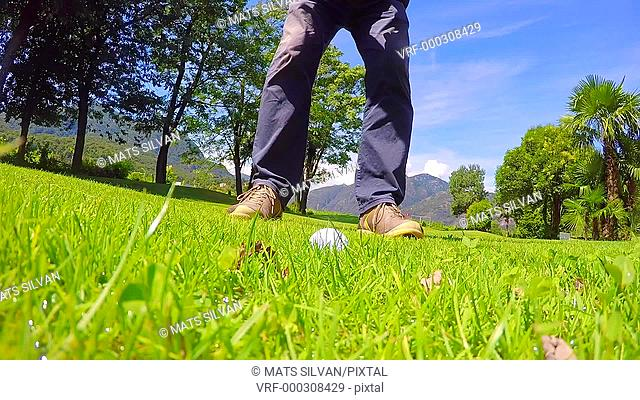 Golfer Making a Golf Swing and Hitting the Golf Ball on Wet Grass in Ticino, Switzerland