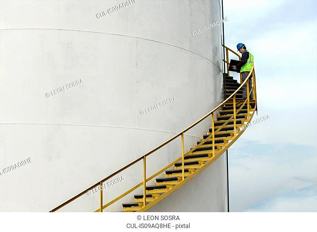 Industrial worker on stairs checking fuel storage tank