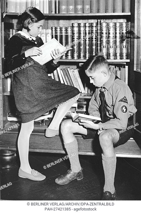 A boy in the uniform of the German Youth and a young girl are reading books in front of a book shelf in October 1938. The National Socialist propaganda from 19...