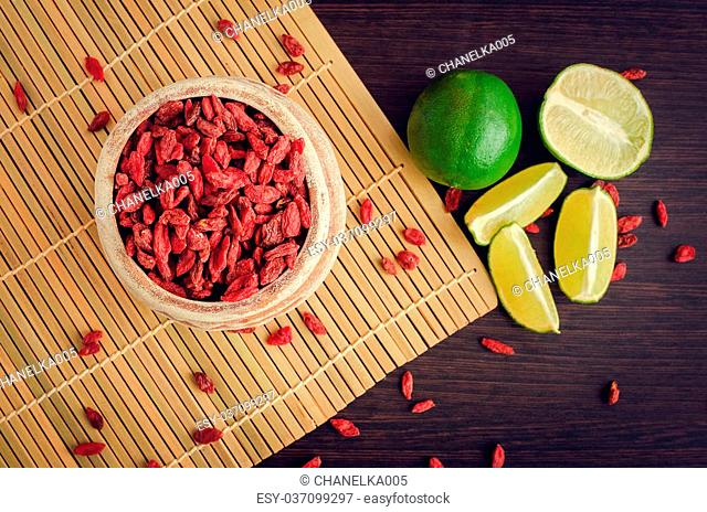 Dried Tibetan goji berries in ceramic bowl with lime on wooden background. Wolfberry for a healthy diet. Healthy food. Alternative medicine