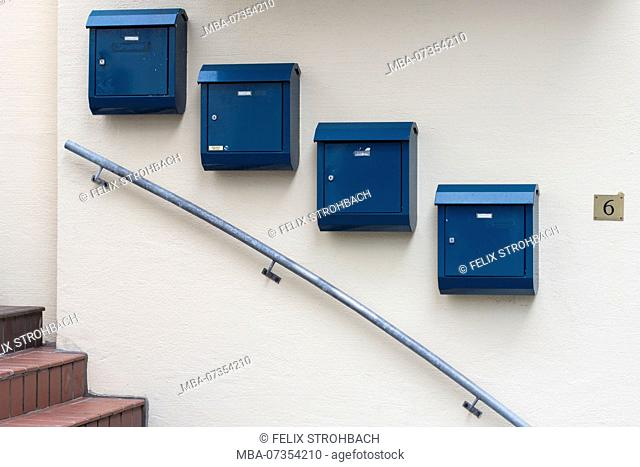 Blue mailboxes along a descending stair railing