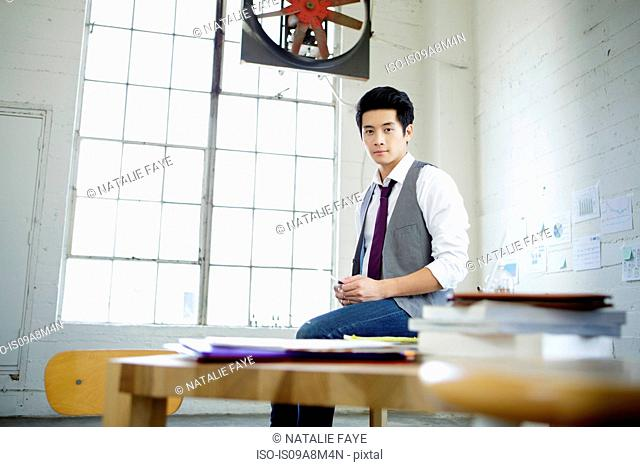 Portrait of young man sitting on office desk