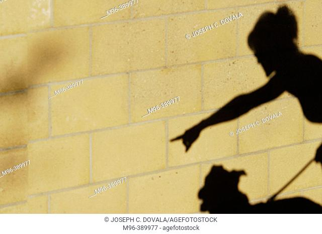 Woman shadow points for dog