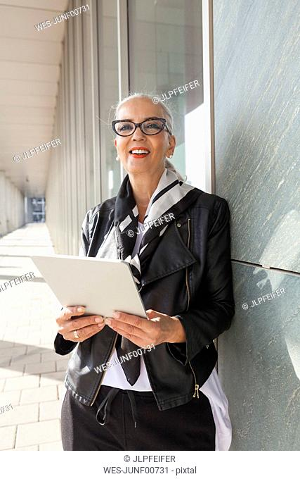 Portrait of fashionable mature woman with tablet