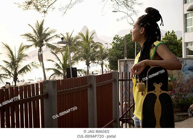 Woman leaning on skateboard, Ipanema, Rio de Janeiro, Brazil