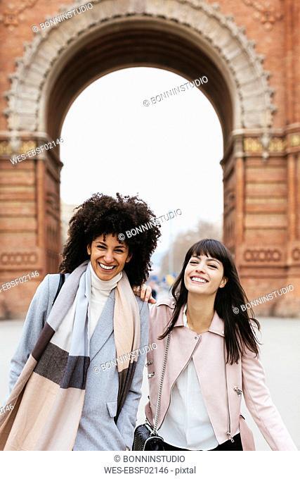 Spain, Barcelona, portrait of two happy women at a gate
