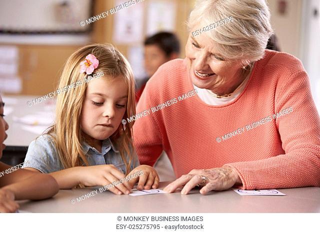 Senior teacher helping schoolgirl in elementary class