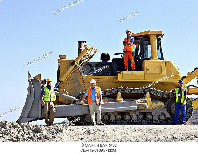 Workers on bulldozer smiling in quarry