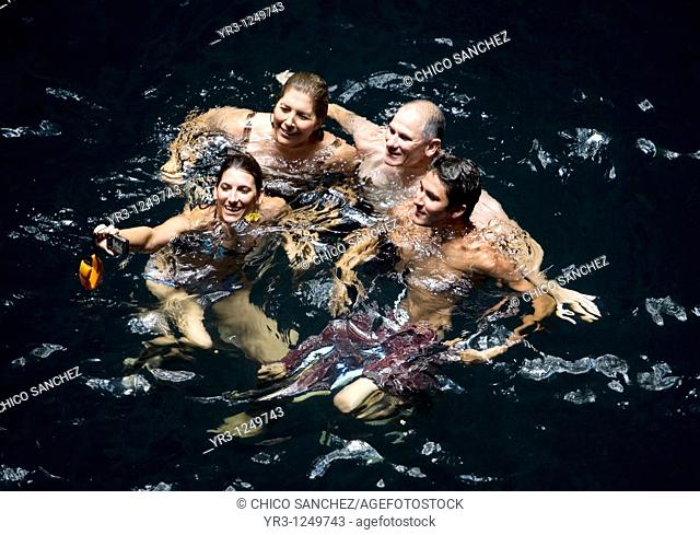 A family takes their picture as they swim in Cenote Ikil, a natural underground pool, in Yucatan state in Mexico's Yucatan peninsula