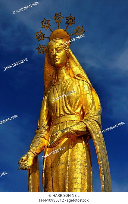 Beautiful Gold statue of the virgin Mary standing on the top of an ancient pass between Italy and Switzerland. the halo containing snowflakes