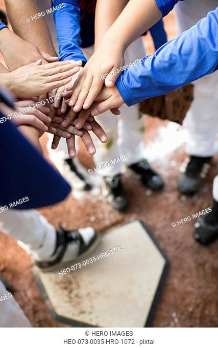 View from above of baseball players hands over hands at homeplate