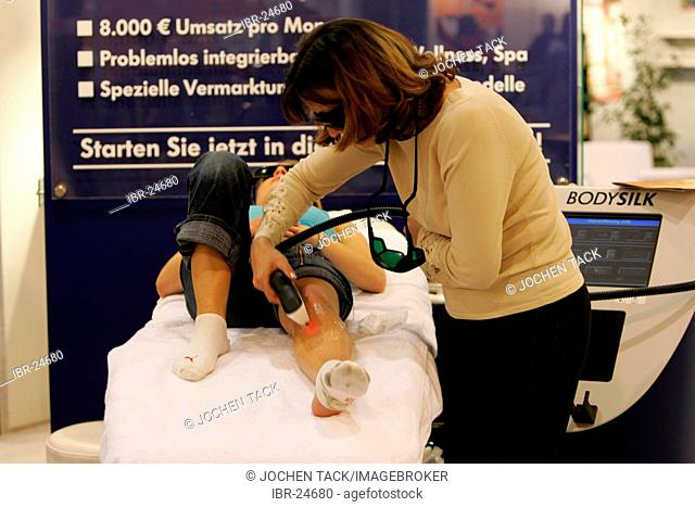 DEU, Germany, Essen : FIBO, Fitness and leisure exhibition. Lasertherapy wit a laser to pick hairs from arms and legs