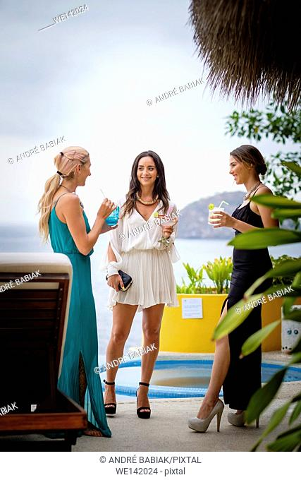 Three young attractive women in elegant dresses at an outdoor cocktail party in Puerto Vallarta, Mexico