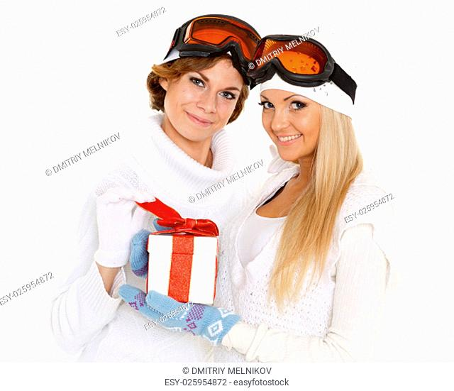 Two young pretty women in winter clothes and ski glasses with gift box on a white background. Winter sports