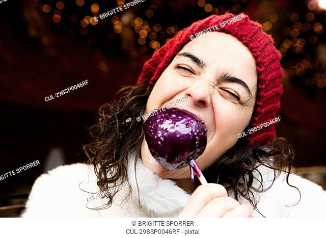 Woman taking a bite of candied apple