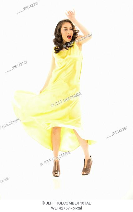 Beautiful young woman dancing in vintage yellow dress, full length in brown heels, one arm raised