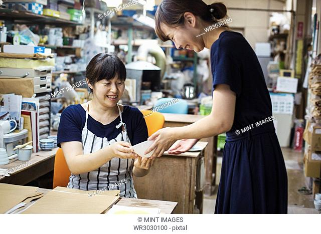 Two smiling women sitting and standing in a workshop, looking at Japanese porcelain bowl