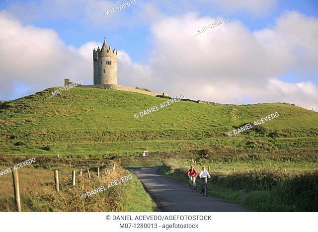 Cycling near Doolin, Doonagore castle, Co Clare, Ireland, Europe
