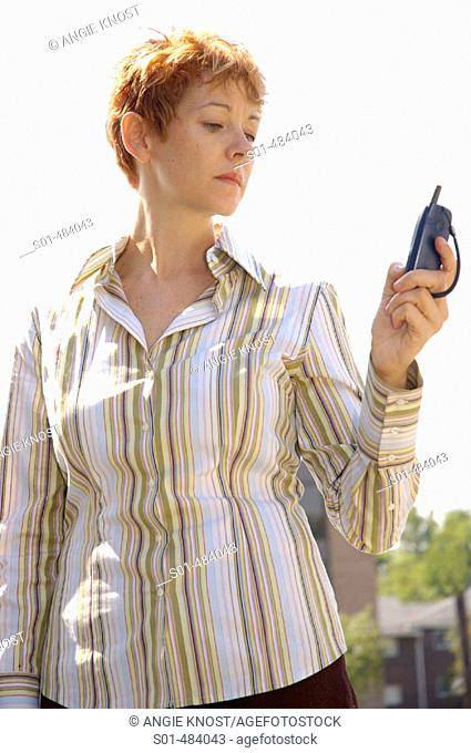 Woman / mother age 30 -40, casually dressed in striped button-down shirt, outdoors, looking at cell phone