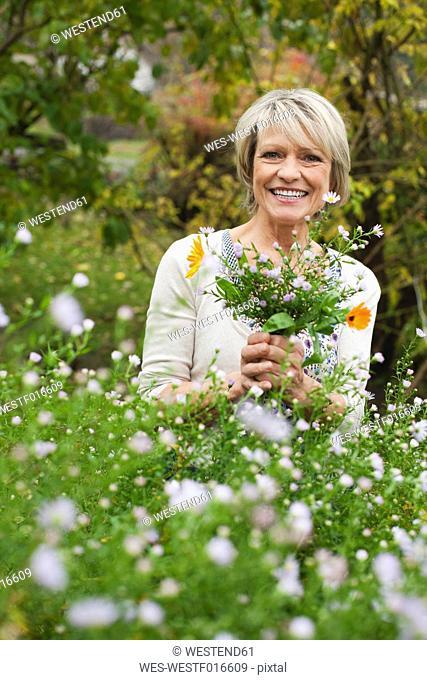 Germany, Kratzeburg, Senior woman in garden, smiling, portrait