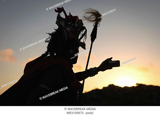 Silhouette of maasai man taking selfie with mobile phone