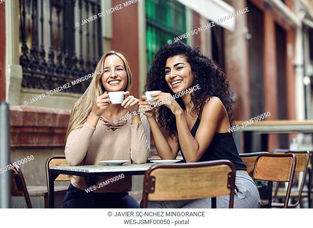 Two happy friends drinking coffee in sidewalk cafe