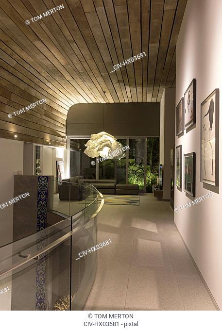 Illuminated modern, luxury home showcase interior with chandelier
